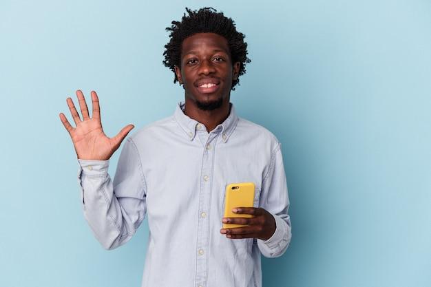 Młody człowiek african american posiadania telefonu komórkowego na białym tle na niebieskim tle uśmiechający się wesoły wyświetlono numer pięć palcami.