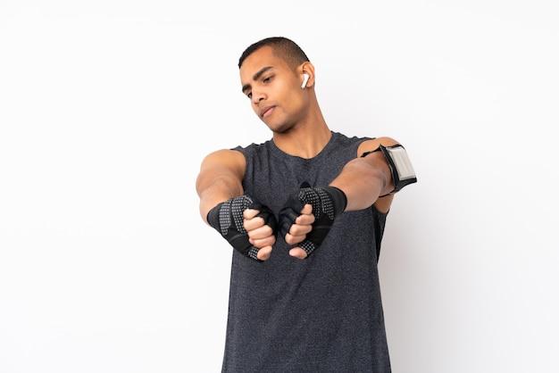 Młody człowiek african american sportu na pojedyncze ramię rozciąganie białej ściany