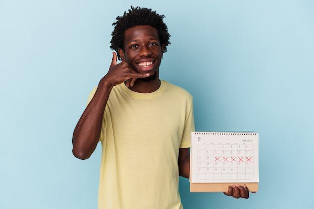 Młody człowiek african american, trzymając kalendarz na białym tle na niebieskim tle pokazując gest połączenia z telefonu komórkowego palcami.