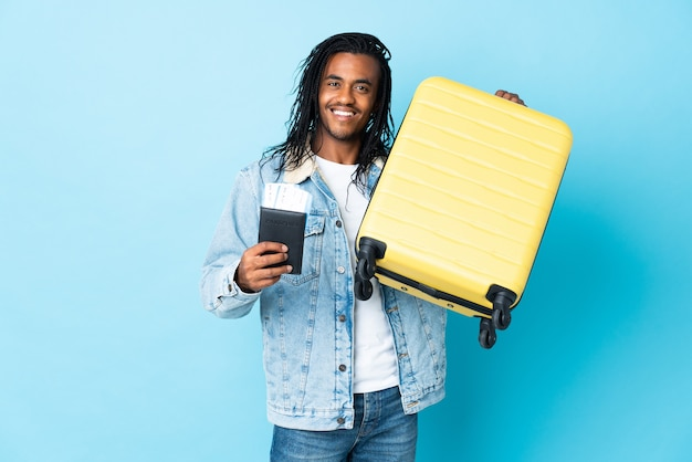 Młody człowiek african american z warkoczami na białym tle na niebieskim tle w wakacje z walizką i paszportem