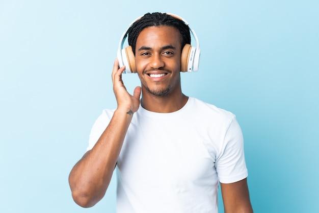 Młody człowiek african american z warkoczami na niebiesko słuchania muzyki