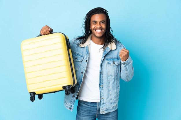 Młody człowiek african american z warkoczykami na niebiesko na wakacjach z walizką podróżną