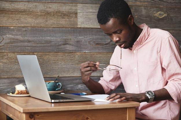 Młody człowiek african-american za pomocą laptopa