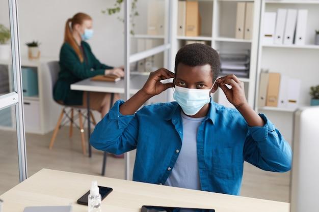 Młody człowiek african-american zakładanie maski podczas pracy przy biurku w biurze po pandemii