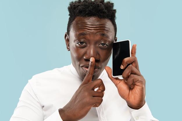 Młody człowiek afro-amerykański na białym tle na niebieskim tle studio, koncepcja ludzkich emocji