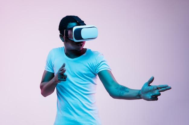 Młody człowiek afro-amerykański, wskazując i używając okularów vr w świetle neonu na gradientowym tle