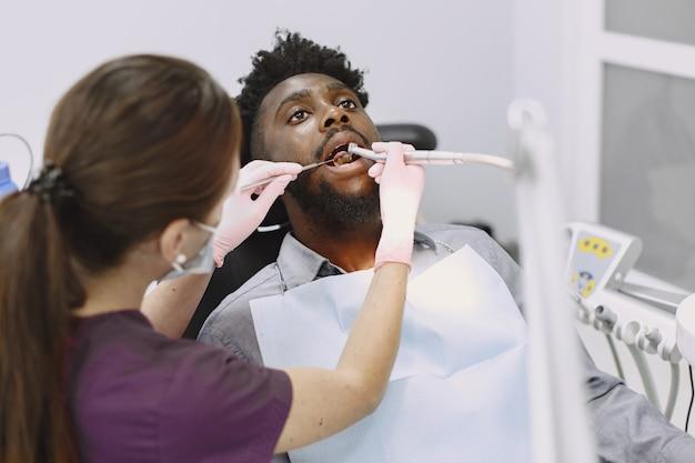 Młody człowiek afroamerykanin. facet odwiedzający gabinet dentystyczny w celu zapobiegania jamy ustnej. mężczyzna i znany lekarz podczas kontroli zębów.