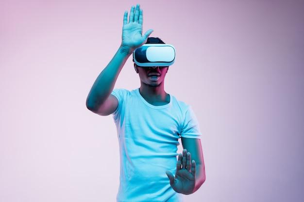 Młody człowiek afroamerykanin gra i używa okularów vr w świetle neonu na gradiencie