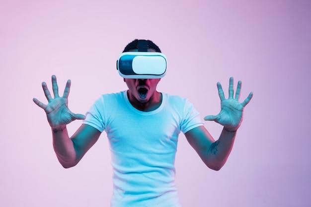 Młody człowiek afroamerykanin gra w okularach vr w świetle neonu na gradientowym tle. portret mężczyzny