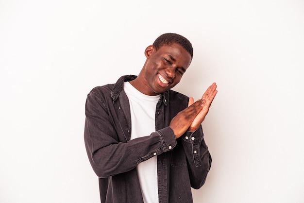 Młody człowiek afroamerykanin na białym tle czuje się energiczny i wygodny, pocierając ręce pewnie.