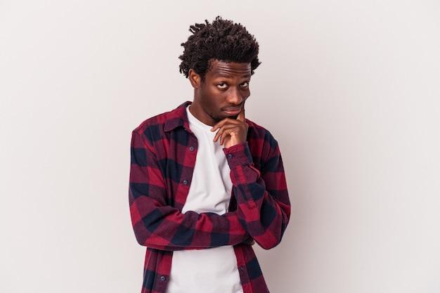 Młody człowiek afroamerykanin na białym tle kontemplując, planując strategię, myśląc o sposobie prowadzenia biznesu.