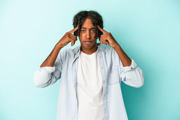 Młody człowiek afroamerykanin na białym tle na niebieskim tle koncentruje się na zadaniu, trzymając palce wskazujące wskazujące głowę.