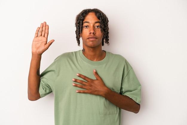 Młody człowiek afroamerykanin na białym tle składa przysięgę, kładąc rękę na klatce piersiowej.