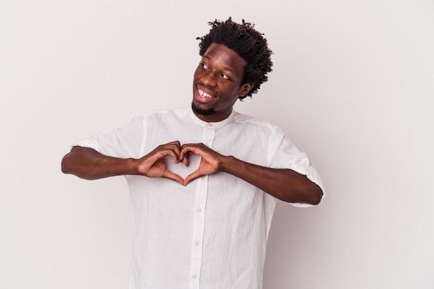 Młody człowiek afroamerykanin na białym tle uśmiechający się i pokazujący kształt serca rękami.