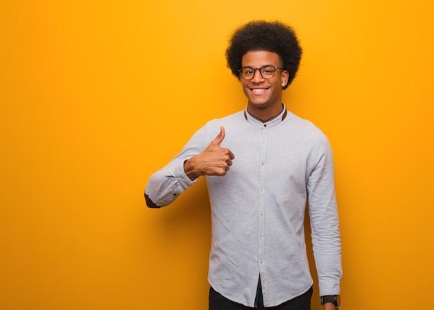 Młody człowiek afroamerykanin na pomarańczowej ścianie uśmiechnięty i podnoszący kciuk do góry