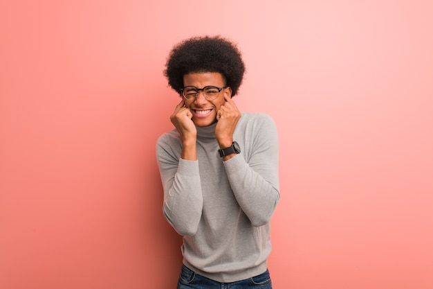 Młody człowiek afroamerykanin na różowej ścianie obejmujące uszy rękami