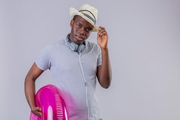 Młody człowiek afroamerykanin podróżnik w letnim kapeluszu ze słuchawkami na szyi, trzymając nadmuchiwany pierścień, patrząc pewnie dotykając jego kapelusza