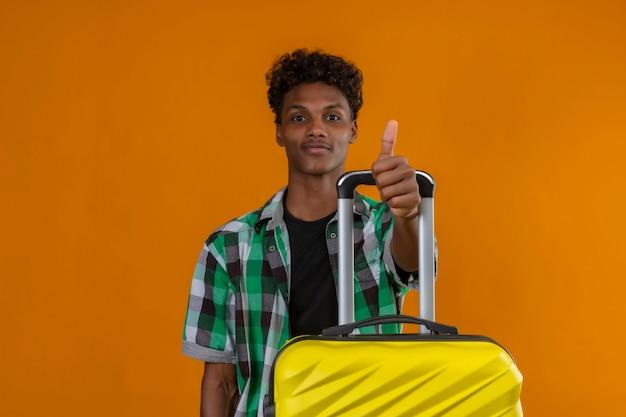 Młody człowiek afroamerykanin podróżnik z walizką uśmiechnięty pokazując kciuki do góry