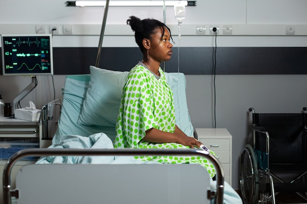 Młody człowiek afroamerykanin siedzi na łóżku na oddziale szpitalnym z gorączką, chorobami, chorobami. chory nastolatek z oksymetrem pod ręką, sprzętem medycznym i pulsometrem do powrotu do zdrowia
