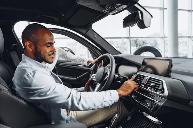 Młody człowiek afroamerykanin siedzi w nowym samochodzie w salonie samochodowym i rozglądając się wewnątrz