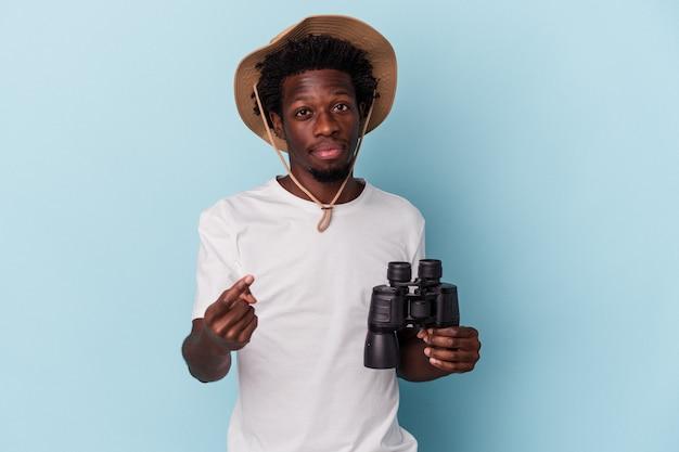 Młody człowiek afroamerykanin trzyma lornetkę na białym tle na niebieskim tle, wskazując palcem na ciebie, jakby zapraszając się bliżej.