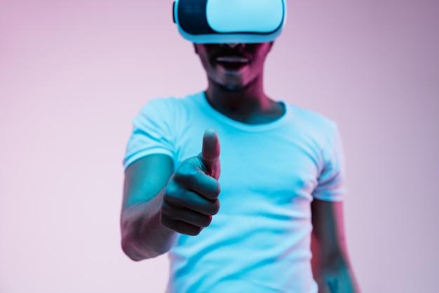 Młody człowiek afroamerykanin w okularach vr w świetle neonu na gradientowym tle. portret mężczyzny