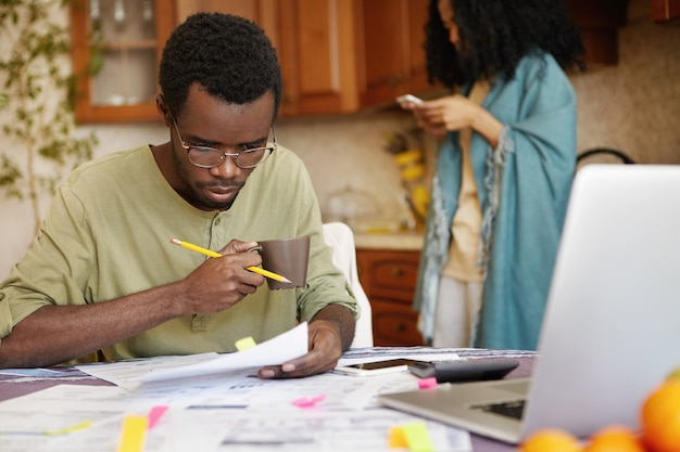 Młody człowiek afroamerykanin w szklankach pije kawę, zajęty obsługą finansów
