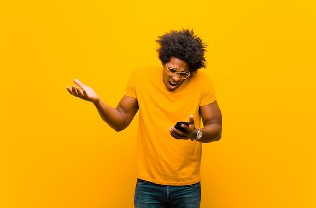 Młody człowiek afroamerykanin z inteligentny telefon przed pomarańczowym bac