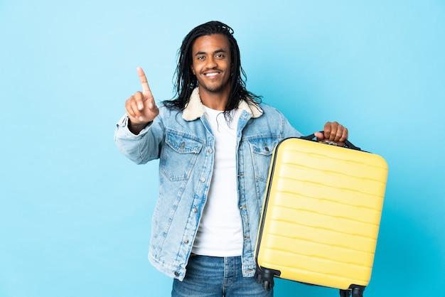 Młody człowiek afroamerykanin z warkoczami na białym tle na niebieskiej ścianie w wakacje z walizką podróżną i licząc jeden