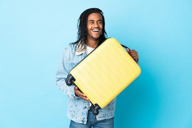 Młody człowiek afroamerykanin z warkoczami na białym tle na niebieskiej ścianie w wakacje z walizką podróżną