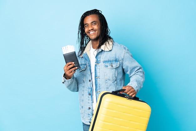 Młody człowiek afroamerykanin z warkoczykami na białym tle na niebieskiej ścianie w wakacje z walizką i paszportem