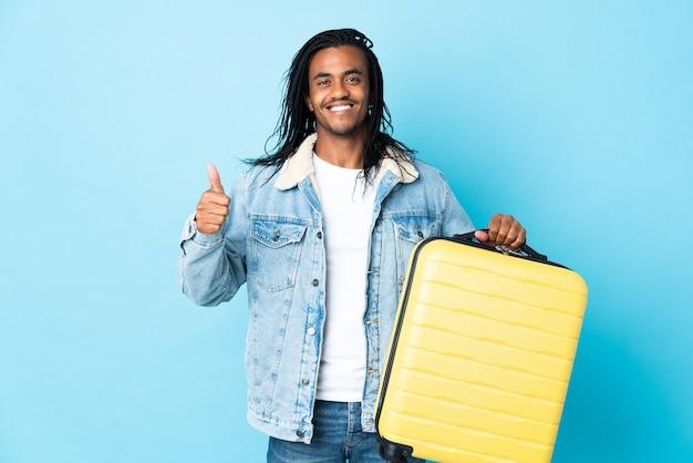Młody człowiek afroamerykanin z warkoczykami na białym tle na niebieskiej ścianie w wakacje z walizką podróżną iz kciukiem do góry