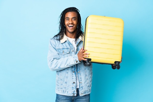 Młody człowiek afroamerykanin z warkoczykami na białym tle na niebieskim tle w wakacje z walizką podróżną i zaskoczony