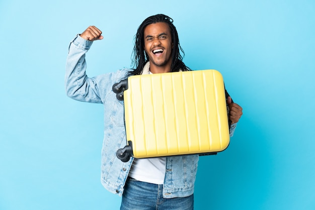 Młody człowiek afroamerykanin z warkoczykami na białym tle na niebieskim tle w wakacje z walizką podróżną