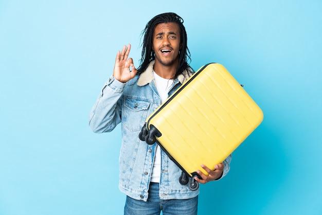 Młody człowiek afroamerykanin z warkoczykami na niebiesko na wakacjach z walizką podróżną i czyniąc znak ok
