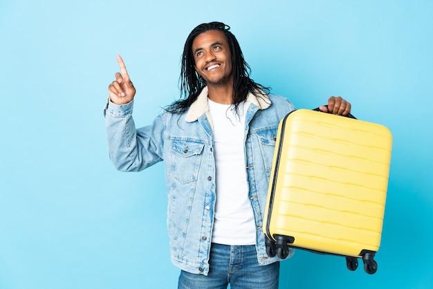Młody człowiek afroamerykanin z warkoczykami na niebiesko na wakacjach z walizką podróżną i skierowaną w górę