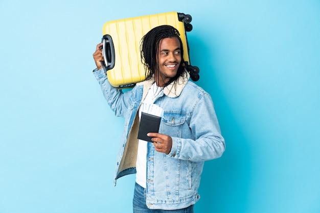 Młody człowiek afroamerykanin z warkoczykami na niebiesko w wakacje z walizką i paszportem
