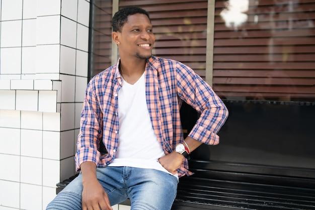 Młody człowiek afroamerykanin zrelaksowany i cieszący się siedząc przy wystawie sklepu na ulicy