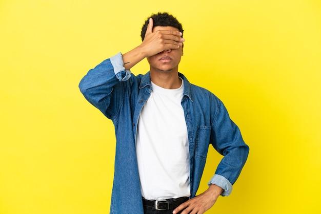 Młody człowiek afroamerykanów na białym tle na żółtym tle zasłaniając oczy rękami. nie chcę czegoś widzieć