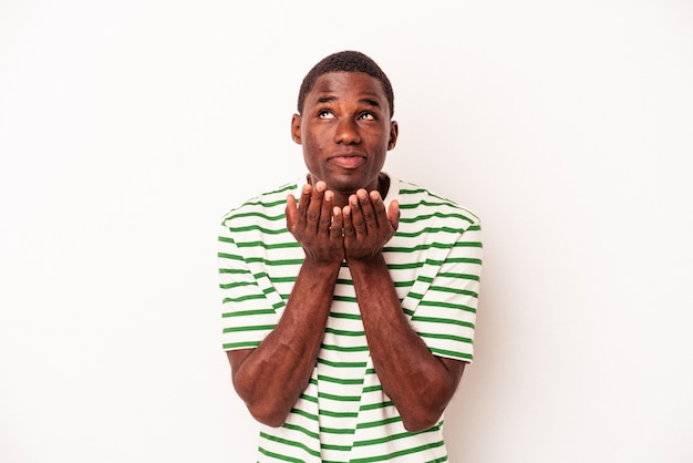 Młody człowiek afroamerykanów na białym tle składane usta i trzymając dłonie, aby wysłać pocałunek powietrza.