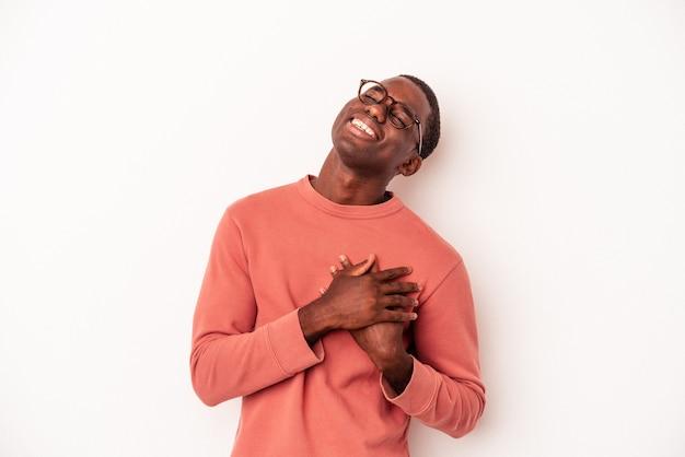 Młody człowiek afroamerykanów na białym tle śmiejąc się trzymając ręce na sercu, pojęcie szczęścia.