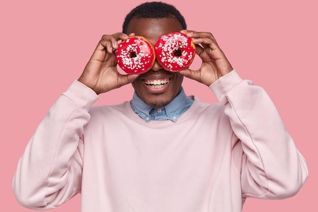 Młody człowiek afroamerykanów posiadający smaczne pączki