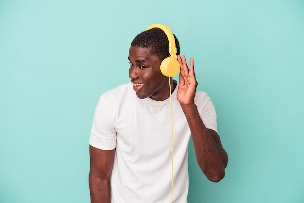 Młody człowiek afroamerykanów słuchania muzyki na białym tle na niebieskim tle próbuje słuchać plotek.