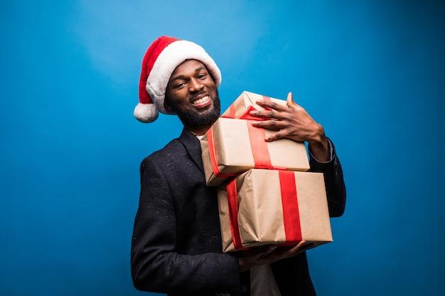 Młody człowiek afroamerykanów ubrany w kapelusz santa oferuje prezenty