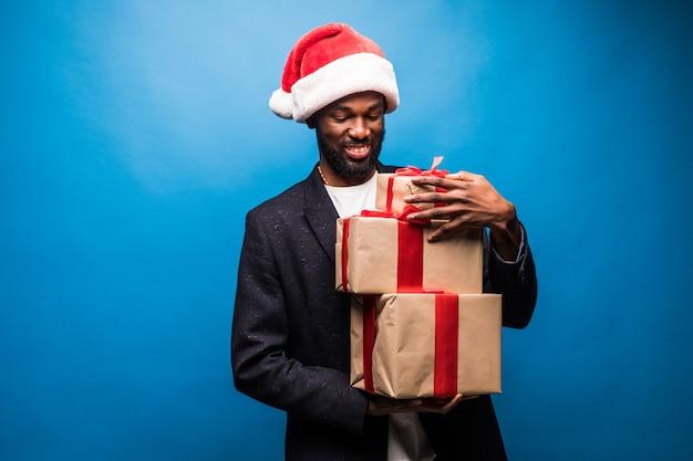 Młody człowiek afroamerykanów ubrany w santa kapelusz gospodarstwa prezenty