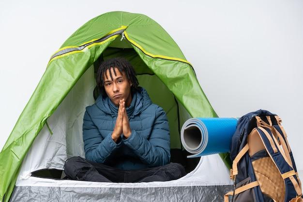Młody człowiek afroamerykanów w środku namiot zielony camping trzyma dłoń razem. osoba prosi o coś