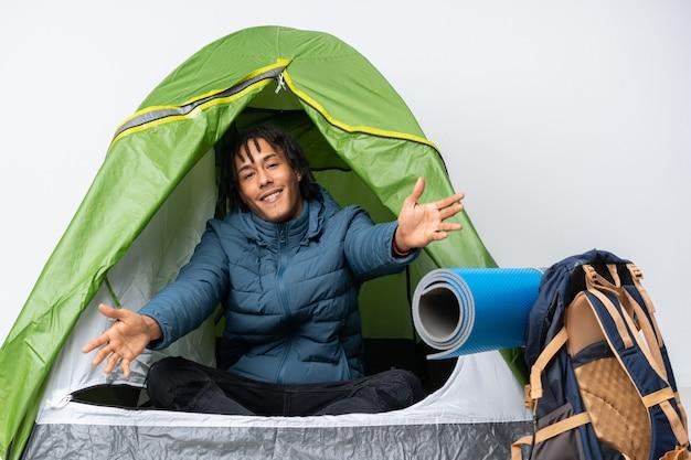 Młody człowiek afroamerykanów w środku zielony namiot kempingowy prezentacji i zapraszając do strony