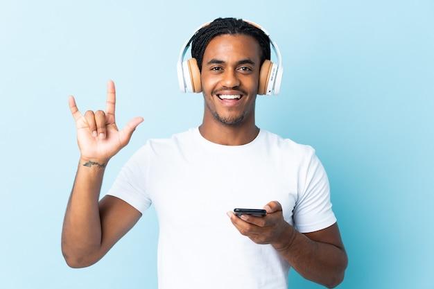 Młody człowiek afroamerykanów z warkoczami na białym tle na niebieskim tle słuchanie muzyki za pomocą telefonu komórkowego gest rocka