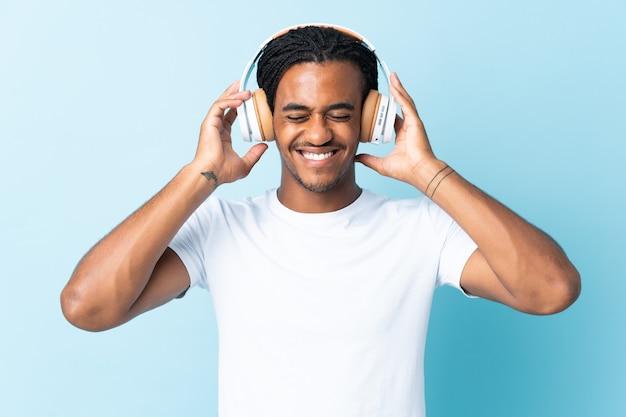 Młody człowiek afroamerykanów z warkoczykami na białym tle na niebieskim tle słuchania muzyki