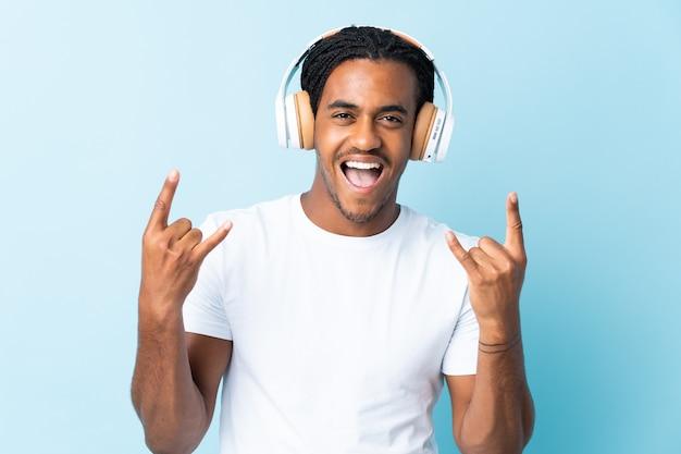 Młody człowiek afroamerykanów z warkoczykami na niebiesko słuchania muzyki, dokonując gestu rocka